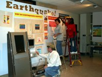 Mark Steed, Exhibit Specialist for the Arkansas State University Museum, together with Sign Shop staff Jerilyn Miller and Kaye Childs, puts finishing touches on the newest exhibit at the ASU Museum.  Entitled Earthquake!, the exhibit was designed by ASU Museum curator Julie K. MacDonald.