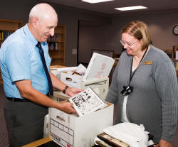 Dr. Joel Gambill, left, and archivist Malissa Davis examine a box of John Robert Starr's papers, a major historical gift to Arkansas State University's Department of Archives and Special Collections. Starr was former Associated Press Bureau Chief in Little Rock and became managing editor of the Arkansas Democrat in 1978, where he wrote a daily column. Starr died in 2000.