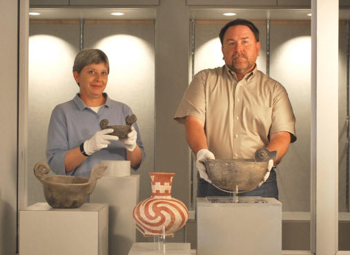 "Heritage Studies PhD students Leslie Hester, left, and Marlon Mowdy display rarely seen examples of Native American pottery from the exhibition, ""Portals of the Soul,"" opening at the ASU Museum on Thursday, July 16, as part of the three-day celebration, ""Our Awesome Ancestors: Celebrate Human Ingenuity."""