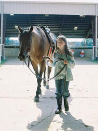Young equestrian Kate Zibluk  leads her horse during a previous ASU Equine Center Horse Camp session.